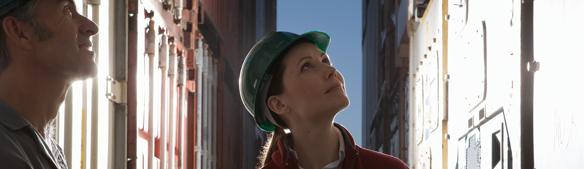 Man and woman standing between cargo containers, wearing hard hats